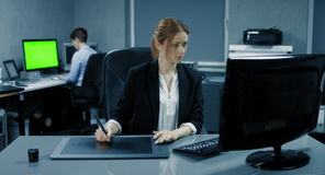 4K: Een bedrijfsvrouw werkt aan een grafiektablet bij haar Desktop Een andere bedrijfsvrouw werkt op de achtergrond met een gr. stock video