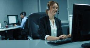 4K: Een callcenterteam werkt in hun bureau De vrouw in de voorzijde gebruikt een hoofdtelefoon stock video