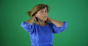4k - Een elegante vrouw maakt haar haar op het groene scherm in studio recht stock videobeelden