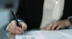 4K: Een jonge manager ondertekent een contract bij haar bureau De vrouw draagt een witte blouse met een zwart jasje stock video