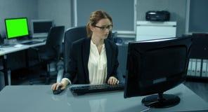 4K: Een jonge manager is zeer geconcentreerd werkend bij haar bureau Zij typt op een computertoetsenbord stock video