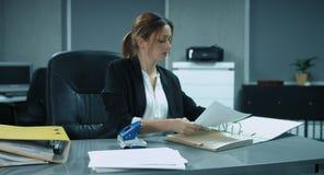4K: Een jonge secretaresse sorteert en dient sommige documenten in het bureau in stock footage