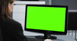 4K: Een jonge secretaresse werkt in haar Bureau De monitor wordt gesloten in chroma groen voor het compositing stock videobeelden