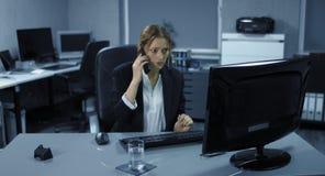 4K: Een jonge werknemer zit tensely in haar bureau Een telefoongesprek stoort haar computerwerk stock footage