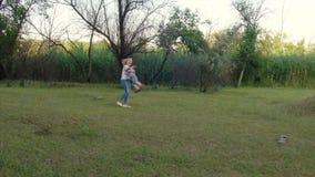 4k een jongen komt langs het park tegen de wapens van zijn moeder stock videobeelden