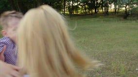 4k een jongen komt langs het park tegen de wapens van zijn moeder stock footage
