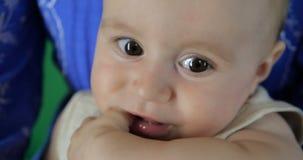 4K - Een kleine baby zuigt zijn vinger dichte omhooggaande, langzame motie stock video