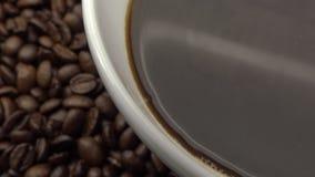 4k een kop van zwarte koffie over Geroosterde Koffiebonen stock footage