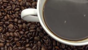 4k een kop van zwarte koffie over Geroosterde Koffiebonen stock videobeelden