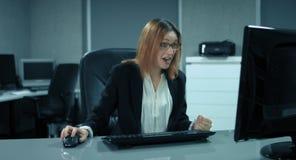 4K: Een secretaresse werkt bij een computer in haar bureau Plotseling is zij zo tevreden zoals Stempel stock video