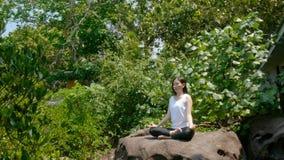 4K een vrouw het praktizeren yoga in meditatie stelt op een rots met groene boom voor milieu tijdens de zomervakantie stock video
