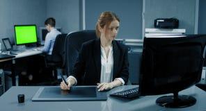 4K: Eine Geschäftsfrau arbeitet an einer Grafiktablette an ihrem Desktop Eine andere Geschäftsfrau arbeitet im Hintergrund mit ei stock video