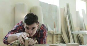 4K el amo del carpintero de los jóvenes mide barras de madera en la industria de la carpintería almacen de metraje de vídeo