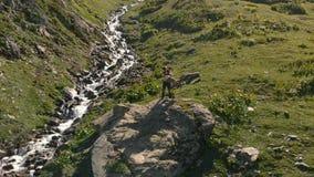 4k - El individuo coge a una muchacha en el valle con un río de la montaña, acción aérea metrajes