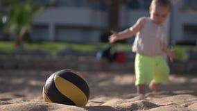 4k - el niño pequeño camina cerca de bola del valleyball en la playa almacen de video