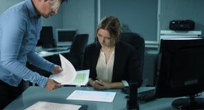 4K: En äldre kollega förklarar ny anställd hur man analyserar de finansiella rapporterna lager videofilmer