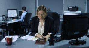 4K: En un puesto de trabajo del ordenador un empleado de sexo femenino joven calcula la corrección de la situación financiera con metrajes