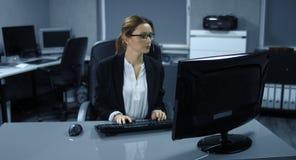 4K: En ung kvinna sitter ner till hennes datorarbetsstation och startar att läsa henne poster och att svara stock video