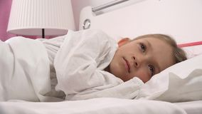 4K enfant réfléchi triste dans le lit ne dormant pas, visage songeur éveillé de fille dans la chambre à coucher banque de vidéos