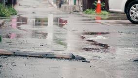 4K establishing shot of rain falling on pavement in an alleyway. stock video