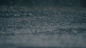 4K establishing shot of rain falling on pavement. stock video