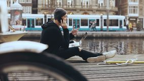 4K European businessman working outside. Man talking on the phone sitting with laptop. River boat and tram passing by. 4K European businessman working outside stock video footage