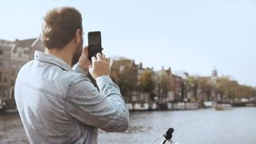 4K European tourist man taking photos on a bridge. Smartphone photography. Adult casual traveller with bicycle. 4K European tourist man in blue shirt taking stock video