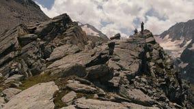 4k - Expedition auf die Oberseite eines hohen felsigen Berges, bewölkter Himmel, Luftaktion stock footage
