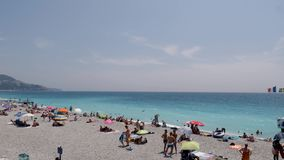 4k Families, Tourists and Locals sunbathing and relaxing on Nice famous pebble beach on French Riviera southern coastlin