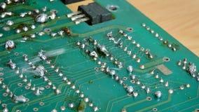 4K fecham-se acima da solda elétrica do tiro na solda na placa de circuito eletrônica da cópia com ligação quente e no fumo com s video estoque