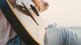 4K Feche acima da mulher longa do cabelo que joga a guitarra acústica na praia com vento delicado durante o tempo do por do sol,  filme