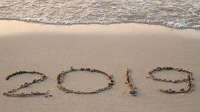 4K Feliz Año Nuevo 2019 el año 2018 escribe en la playa arenosa, cambio del chapoteo de la onda al año 2019 cuenta descendiente p metrajes