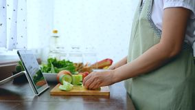 4K. female hand slicing fresh lettuce, prepare ingredients for cooking follow cooking online video clip on website via tablet. Cooking content on internet stock video footage
