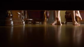 4k, female and male feet view from under the bed. Man and woman hugging and kissing in the bedroom stock video