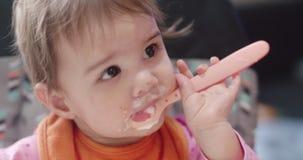 4K Filmowy portret 10 miesięcy stara dziewczynka jest łyżką karmił jogurt zbiory