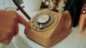 4K finger del uso de la gente que marca un teléfono rotatorio retro del estilo del vintage tinte de la película para el tono del