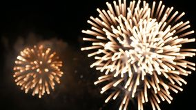 4K. fireworks background. abstract blur of real golden shining fireworks with bokeh lights in the night sky. glowing fireworks stock footage