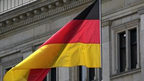 4K. Flag of Germany waving in the wind in front of a historical building stock video