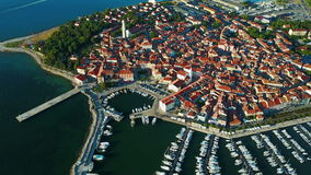4K. Flight over old town Izola in Slovenia, aerial panoramic view with marina at sunset. Adriatic sea coast. Peninsula of Istria stock footage