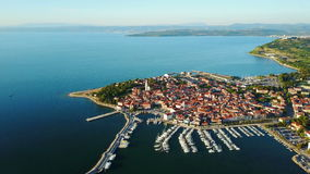 4K. Flight over old town Izola in Slovenia, aerial panoramic view with marina at sunset. Adriatic sea coast. Peninsula of Istria stock video footage