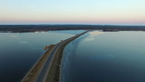 4K. Flight over road in the frozen lake in winter on sunset, aerial view stock footage
