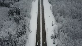 4K. Flight over road in frozen winter forest with driving cars. Aerial panoramic view. Vanishing perspective stock video