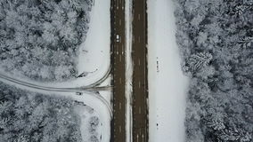 4K. Flight over road in the frozen winter forest with driving cars. Aerial top view stock footage