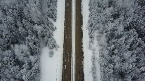 4K. Flight over road in the frozen winter forest with driving cars. Aerial top view.  stock video footage