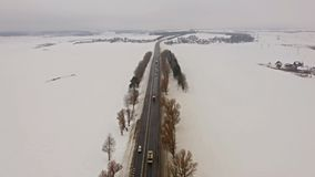4K. Flight over Winter road with driving cars on the north. Aerial panoramic view. Vanishing point perspective stock video footage