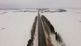 4K. Flight over Winter road with driving cars on the north. Aerial panoramic view. Vanishing point perspective stock footage