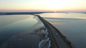 4K Flyg över vägen i den djupfrysta sjön i vinter på solnedgången, flyg- sikt arkivfilmer