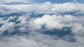 4K flyg- sikt till och med ett flygplanfönster härlig vit fördunklar i bakgrund för blå himmel Lopp förbi luft arkivfilmer