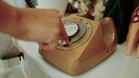 4K folkbruksfinger som ringer en retro roterande tappningstiltelefon filmfärg för tappningsignal gammal telekommunikationteknolog stock video