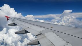4K footage airplane flight. wing of an airplane flying above the white clouds and blue sky. beautiful aerial view from the window. Of the plane on travelling stock video footage
